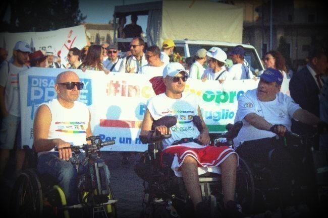 Un momento del corteo 2019: in primo piano tre uomini in sedia a rotelle, dietro loro lo striscione del Disabilioty Pride. Sullo sfondo la folla del corteo.